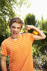 Caucasian teenager squeezing orange with arm