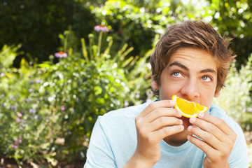 Caucasian teenager eating orange