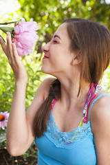 Caucasian teenager smelling flower