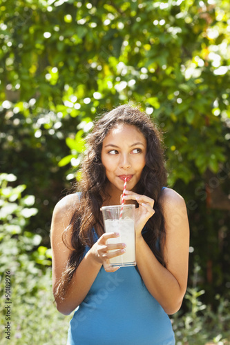 Mixed race woman drinking lemonade outdoors
