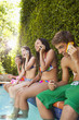 Friends sitting by pool talking on cell phones