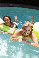 Girls laying on inflatable raft in swimming pool