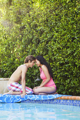 Teenage couple sitting next to swimming pool