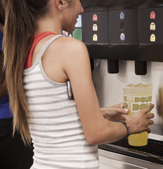 Caucasian woman filling cup with soda from machine