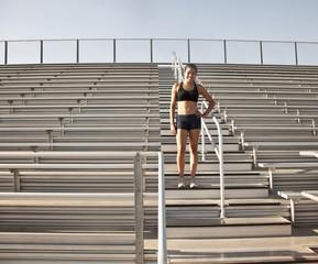 Mixed race runner standing in bleachers