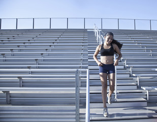 Mixed race runner running down bleacher stairs