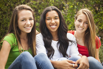 Smiling teenage friends sitting together
