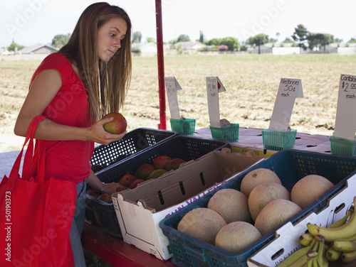 Caucasian teenager shopping at fruit stand