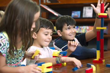 Hispanic students in library playing with blocks