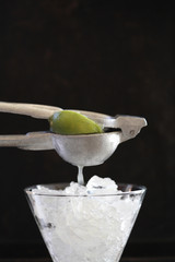 Lime being squeezed over ice