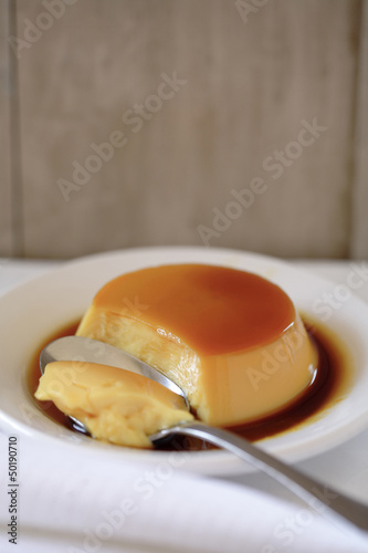Flan on plate with spoon