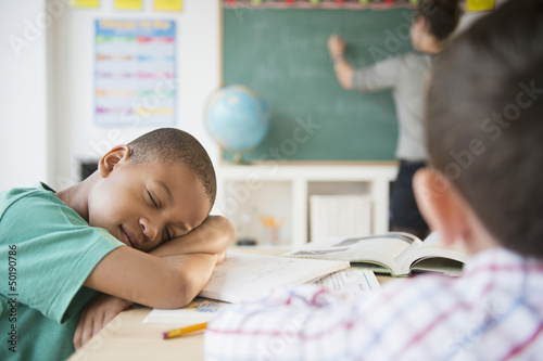 African American boy sleeping in classroom