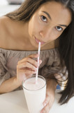Hispanic teenager drinking milk with straw