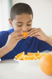 Hispanic boy eating orange sections