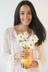 Smiling Hispanic teenager holding flowers