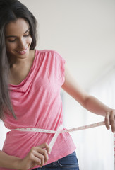 Hispanic teenager measuring her waist