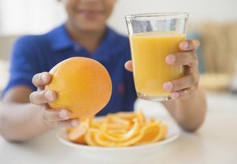 Hispanic boy holding orange and orange juice