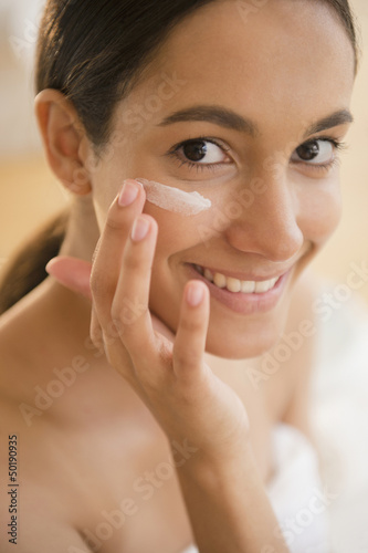 Hispanic teenager putting on face lotion