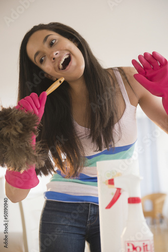 Hispanic teenager singing into a feather duster