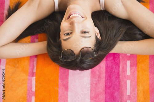 Hispanic teenager laying on towel