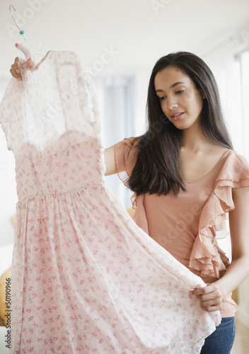 Hispanic teenager looking at dress