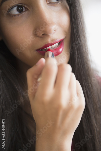 Hispanic teenager putting on lipstick