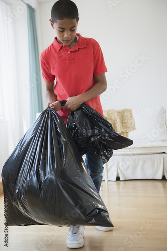 Hispanic boy carrying garbage bag