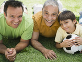 Hispanic grandfather, father and son laying in grass