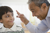Hispanic grandfather offering coin to grandson