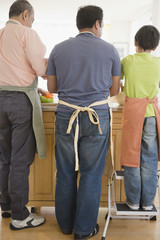 Hispanic grandfather, father and son washing dishes