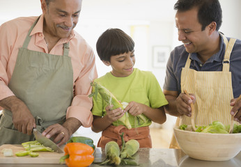 Hispanic grandfather, father and son preparing food