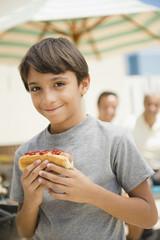 Hispanic boy eating hot dog