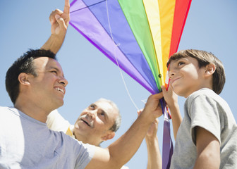 Hispanic grandfather, father and son flying kite