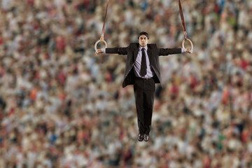 Hispanic businessman hanging from gymnastic rings