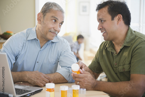 Hispanic son explaining medication to father