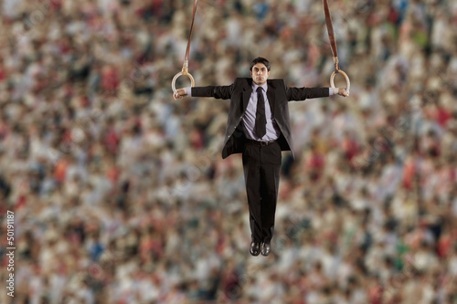 Hispanic businessman hanging from gymnastic rings