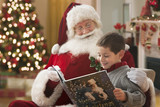 Santa reading book to Caucasian boy