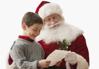 Caucasian boy showing Santa his Christmas list