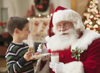 Caucasian boy and Santa sharing cookies