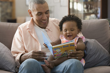 Black father reading book to daughter