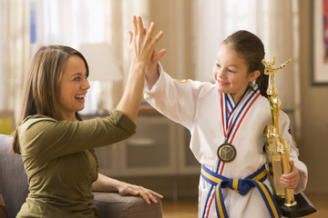 Caucasian mother high-fiving daughter for karate win