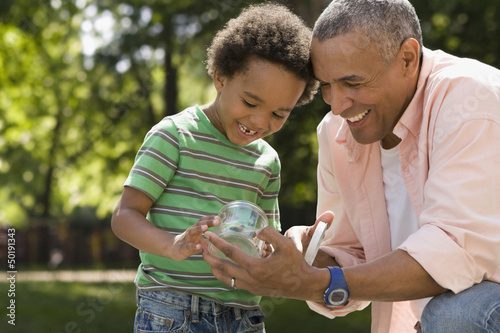 Black father and son looking at insect