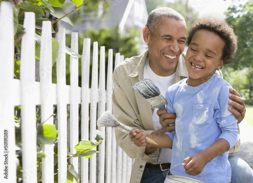 Black father and son painting fence together