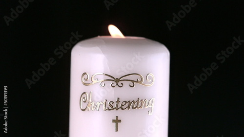 Lit christening candle flickering
