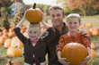 Caucasian father and children holding pumpkins