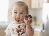 Messy Hispanic baby eating cake