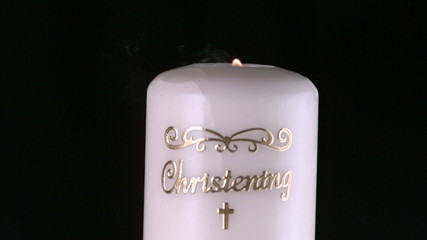 Lit christening candle flickering and going out