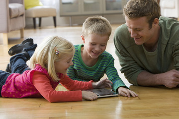 Caucasian father and children using digital tablet