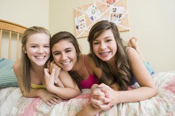 Smiling Caucasian teenage girls in bedroom