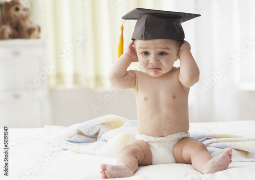 Hispanic baby putting on graduation cap